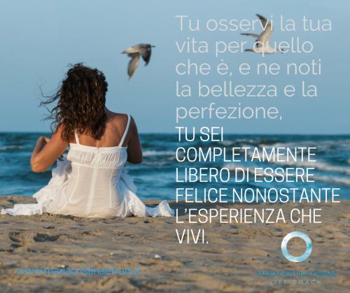 Mariacristina coach in riva al mare con gabbiani e frase: tu sei completamente felice nonostante l'esperienza che vivi.