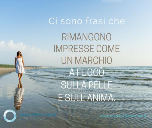 mariacristina coach cammina davanti al mare con frase: ci sono frasi che rimangono impresse come un marchio a fuoco sulla pelle e sull'anima.