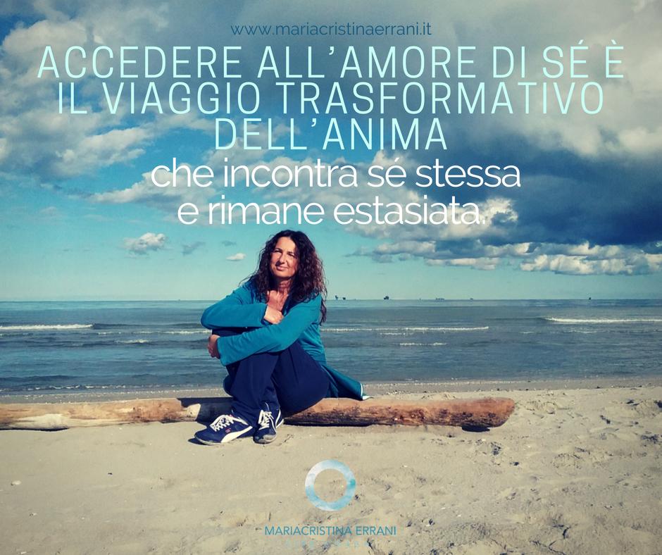 Mariacristina coach seduta su un tronco in spiaggia con frase: accedere all'amore di sè è il viaggio trasformativo dell'anima che incontra sè stessa e rimane estasiata.