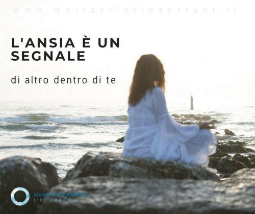 Mariacristina life coach in posizione meditativa sugli scogli con frase: l'ansia è un segnale di altro dentro di te.