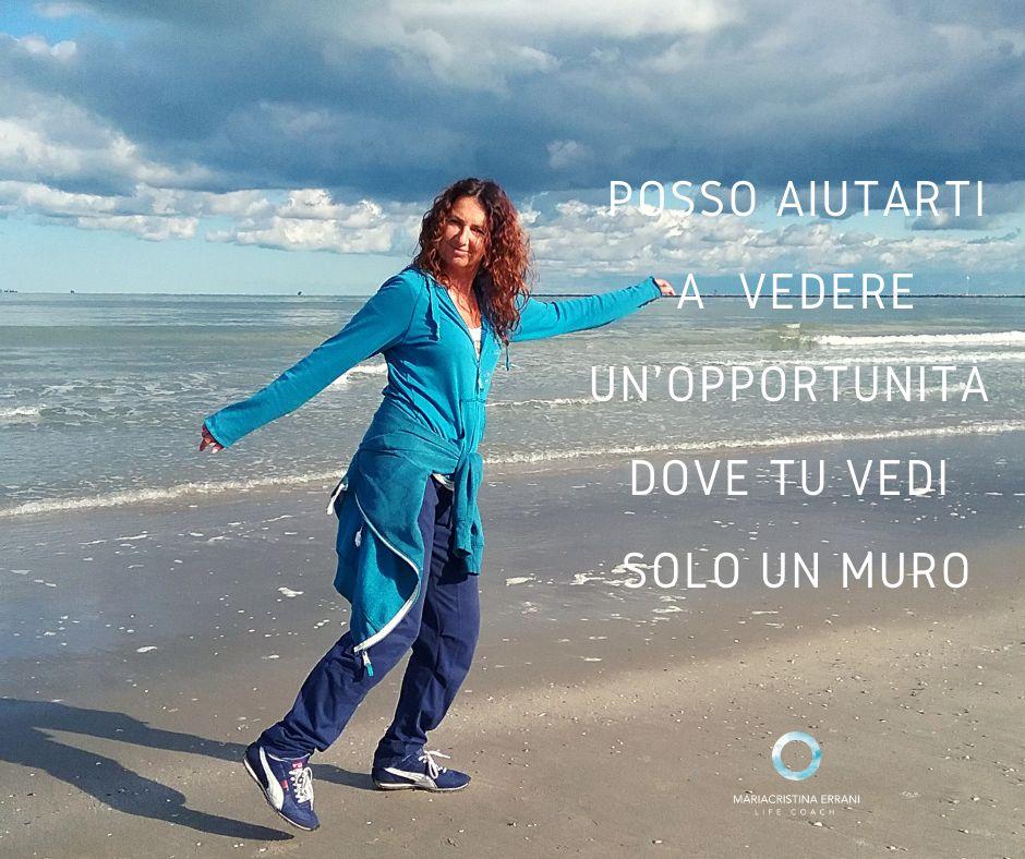 Mariacristina coach in spiaggia indica la direzione con frase: posso aiutarti a vedere una opportunità dove tu vedi solo un muro.