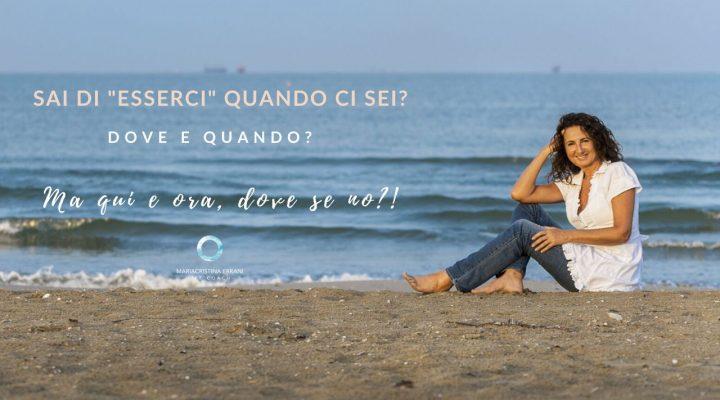Mariacristina coach seduta in spiaggia con frase: Sai di esserci quando ci sei? Dove e quando? Ma qui e ora dove se no?!