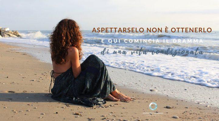 Mariaccristina life coach guarda il mare con scritta: Aspettarselo non è ottenerlo e qui comincia il dramma di una vita condizionata